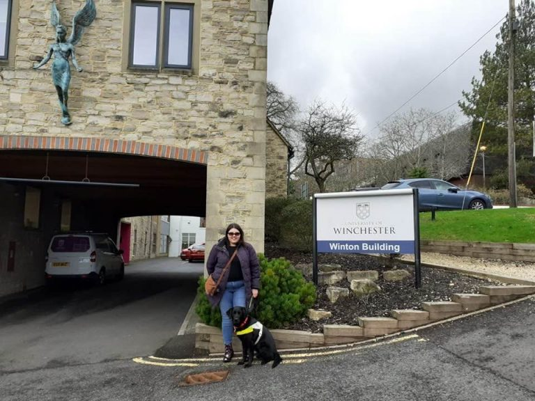 Elin and her black lab guide dog Jazzy stood outside the University of Winchester.
