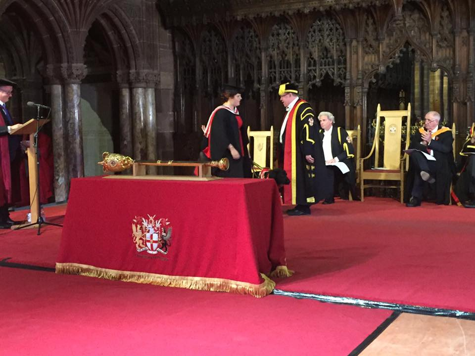 Photo of Elin and Jazzy on stage receiving Elin's degree from the vice chancellor.