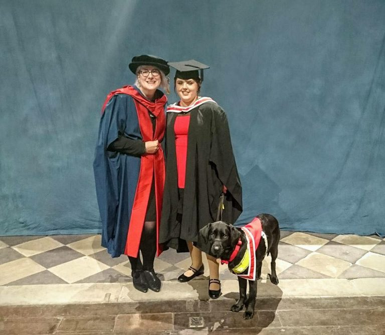 Elin and guide dog Jazzy with a course tutor at graduation both in colours and gown.