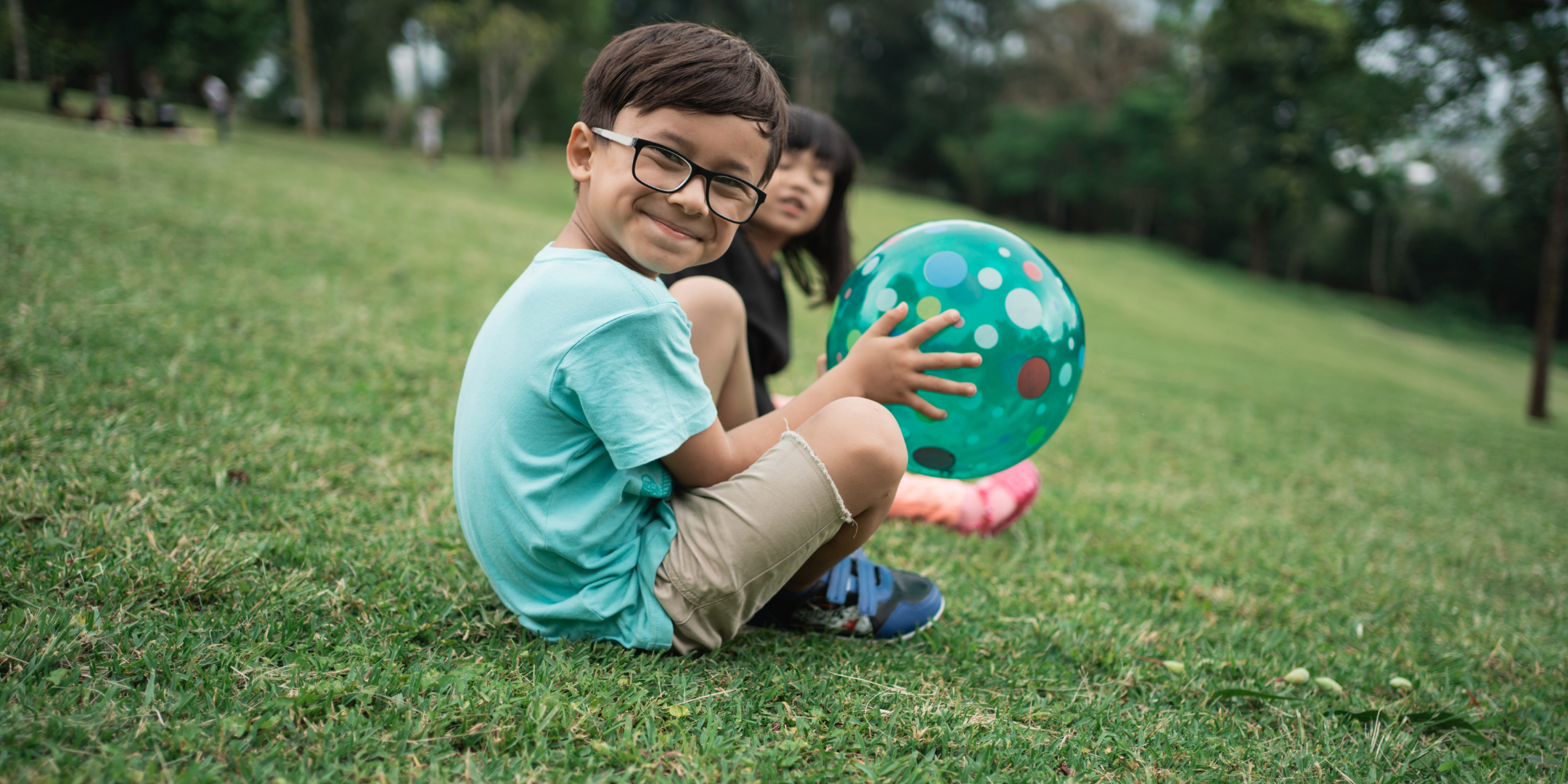 Photo of a little boy wearing glasses, holding a green ball whilst sitting on the grass and smiling at the camera. His little sister sits behind him.