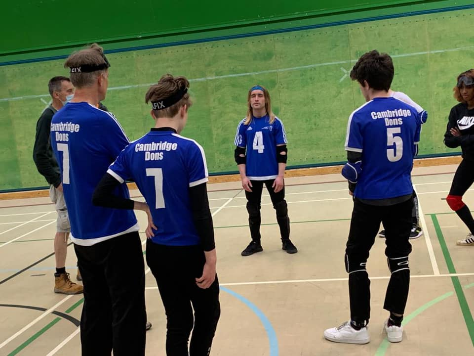 Warren stands in the middle of a group of people in a sports hall, wearing blue and white 'Cambridge Dons' Goalball tops.