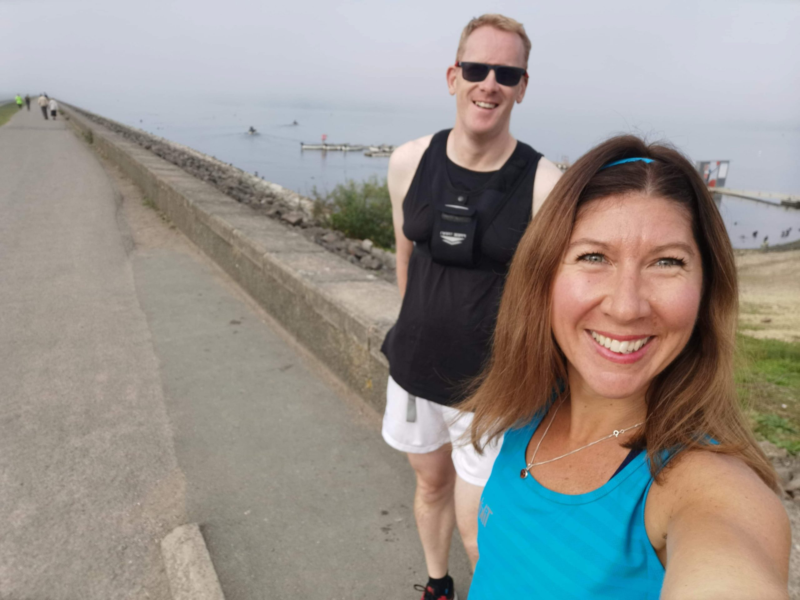 Photo shows Andy wearing black running vest and white shorts with friend and long-distance running partner, Rachel in foreground, wearing blue vest.