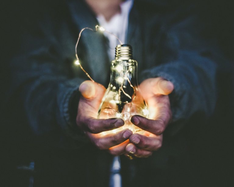 Photo of a pair of hands holding a glass lightbulb with a thin string of LED fairy lights inside.