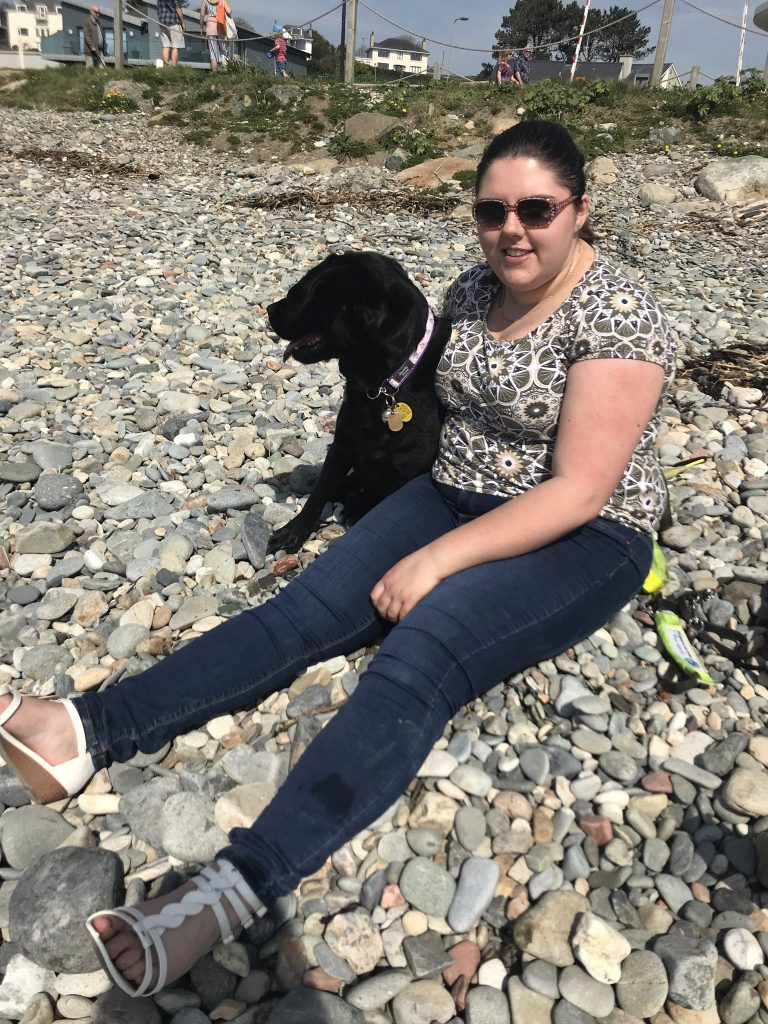 Elin wearing sunglasses, sat next to black lab guide dog Jazzy on a shingle beach.