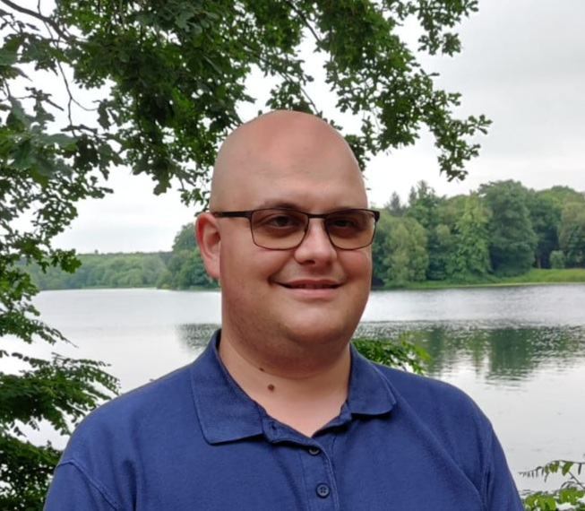 Photo of Nik wearing a blue polo shirt, lake and trees in the background.