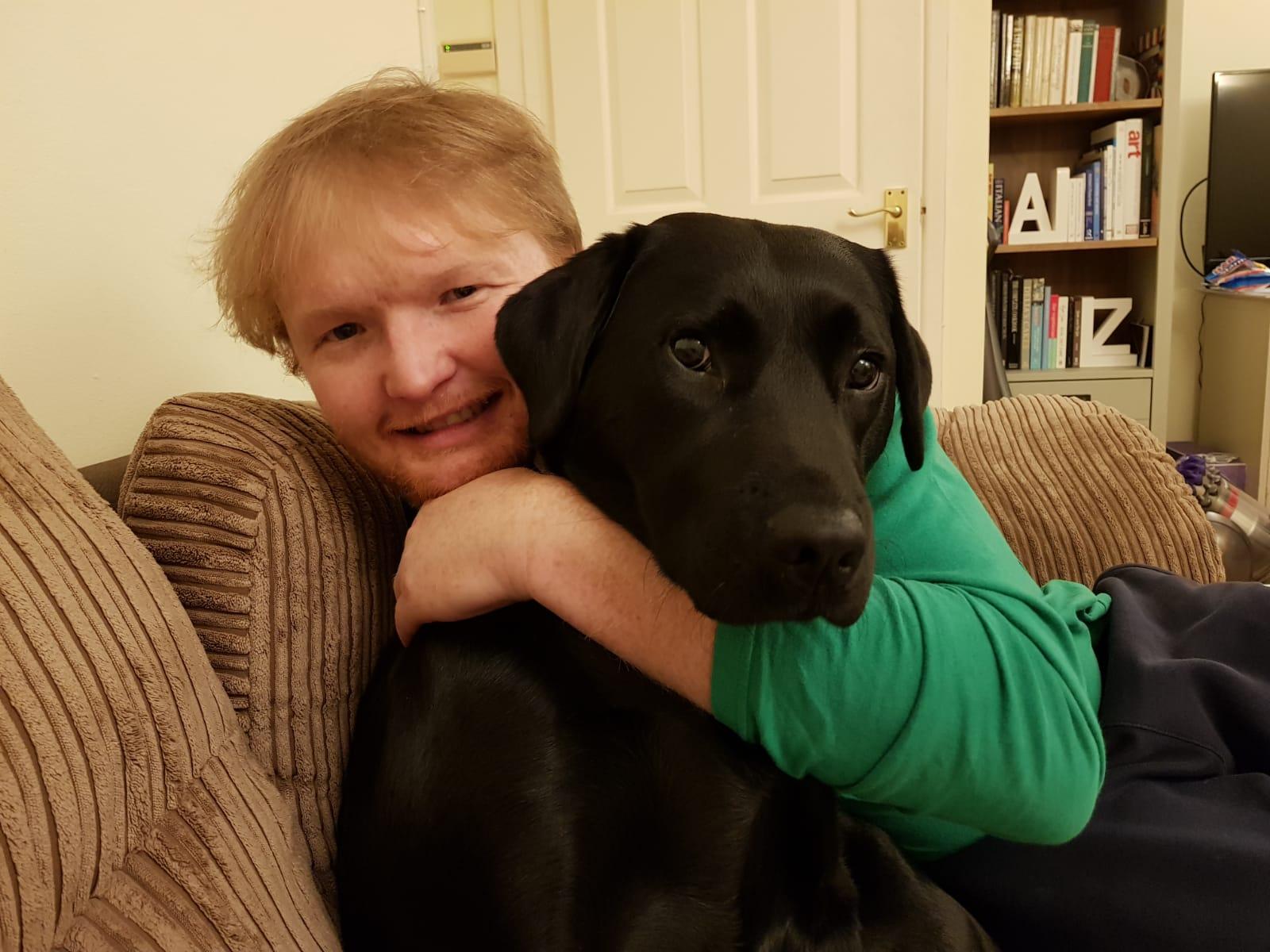 Photo of Nathan cuddling black labrador guide dog Maisie on sofa.
