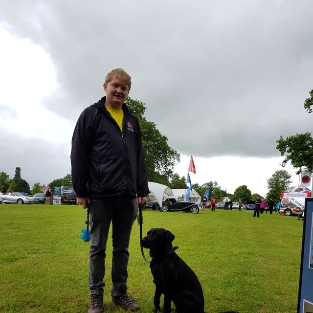 Nathan with black lab guide dog Maisie on a lead, standing in a field with marquees and cars in background.