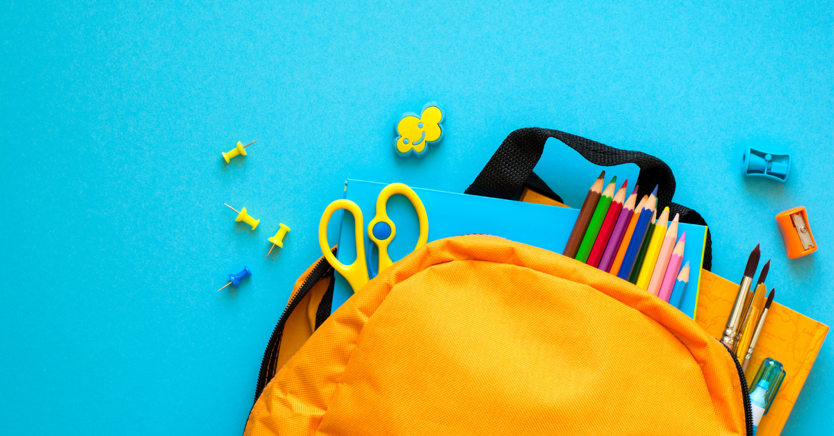 Image shows a bright yellow rucksack lay against a turquoise background. Yellow scissors, pins, colouring pencils and a blue exercise book spill out of the bag.