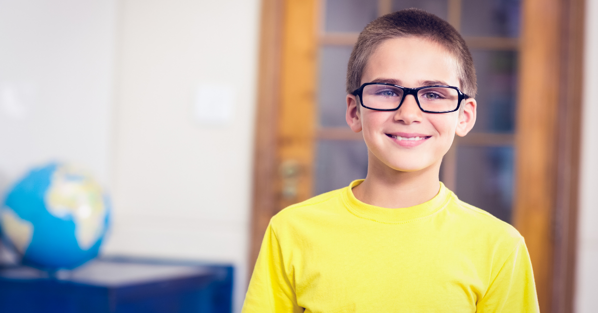 Photo of young boy in yellow t-shirt and glasses with a globe in the background.