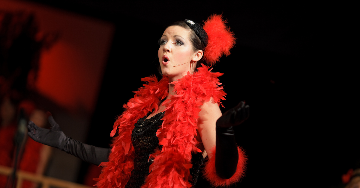 Photo of a female performer on stage wearing a red feather boa and a red feather in her hair. She sings into an ear-piece microphone.