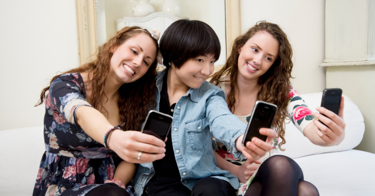 Photo of 3 girls sat in a row all taking a selfie using their smart phones.