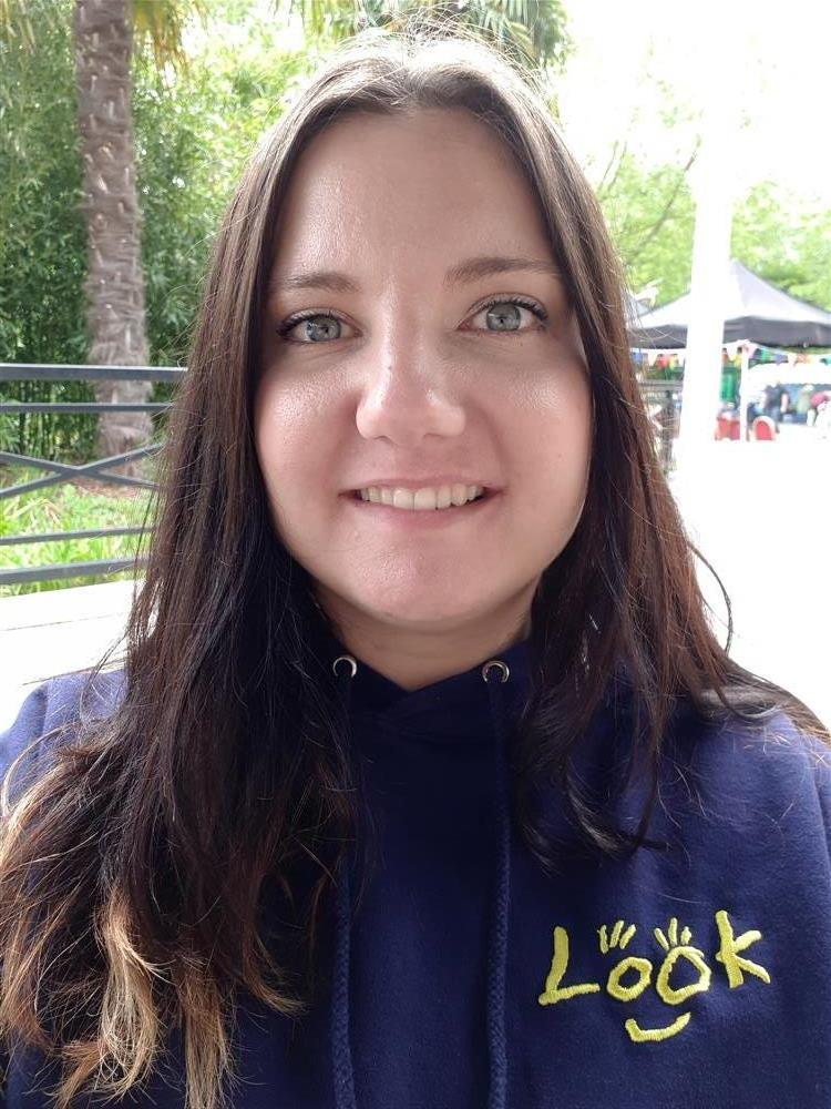Photo of Emma with long brown straight hair, wearing a royal blue LOOK hoodie with the LOOK logo in yellow text.