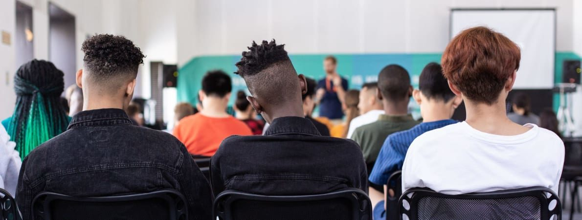 Photo of the backs of a row of 3 students sat in a lecture room.